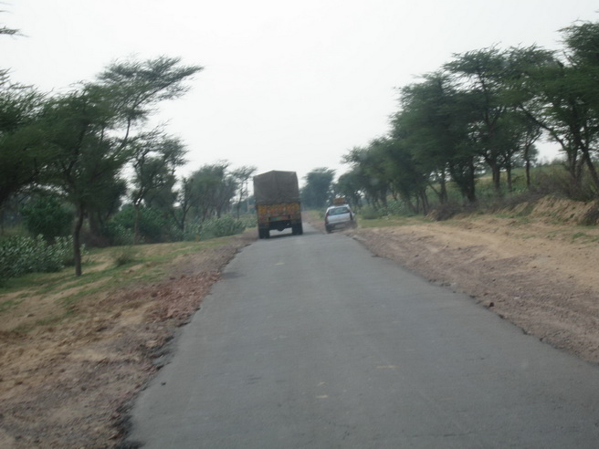 Car passing truck on a narrow road