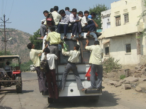 Passengers climbing on top of bus